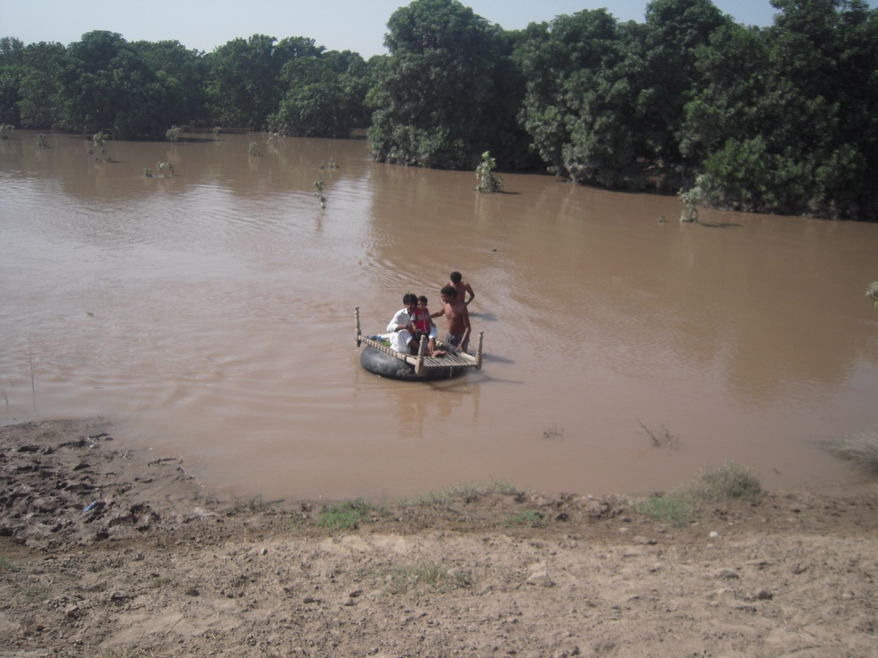 Travelling across the flood waters to villages with a bed on top of a wooden-frame bed