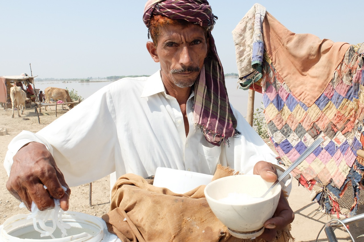 A man selling falooda (a sweet and cold drink made with vermicelli) from his cycle in the khana badosh community as a means of livelihood