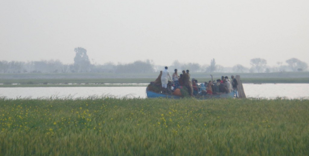 A community from Wilan Village leave their homes on a boat to reach dry areas.